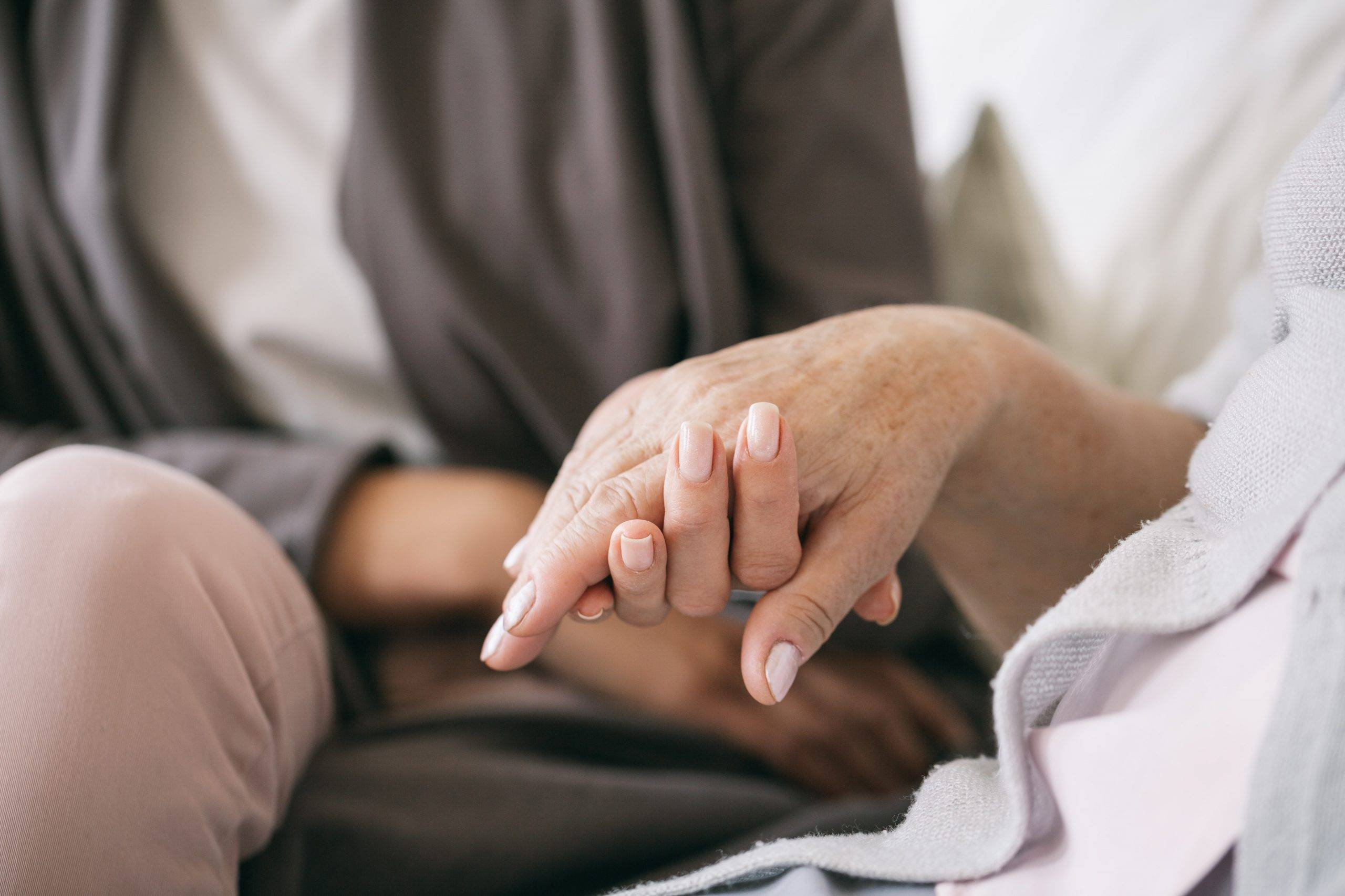 Close up of caregiver holding older woman's hand
